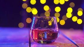 I exponeringsglas av fallande is för whisky kul?r lighting Bokeh i bakgrund arkivfilmer
