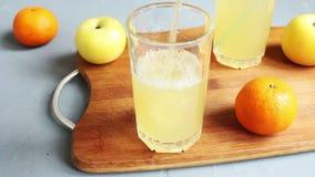 I exponeringsglas som fylls med fruktsaft och förlagt sugrör till drinken arkivfilmer