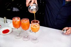 I exponeringsglasen med is häller bartendern coctailar royaltyfria bilder