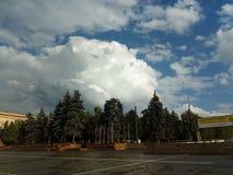 I förgrunden är revolutionfyrkanten i Chelyabinsk såväl som tecknet av åskväderaktivitet i form av stackmolnmoln royaltyfri fotografi