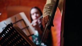 I förgrunden spelar en hand för man` s en stränginstrument, i bakgrunden lekar för en kvinna fiolen lager videofilmer