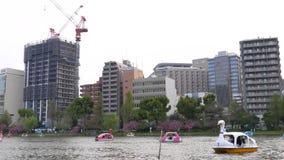 I famalies giapponesi con i bambini galleggiano sulla barca pedale a forza del cigno, Tokyo archivi video