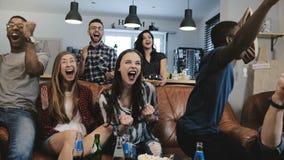 i fan Multi-etnici impazzono la celebrazione dello scopo sulla TV I sostenitori appassionati di calcio gridano con movimento lent Fotografie Stock