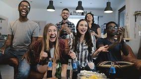 i fan Multi-etnici impazzono la celebrazione dello scopo sulla TV I sostenitori appassionati di calcio gridano con movimento lent Fotografia Stock Libera da Diritti