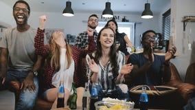 i fan Multi-etnici impazzono la celebrazione dello scopo sulla TV I sostenitori appassionati di calcio gridano con movimento lent Immagini Stock