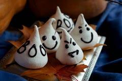 I fantasmi divertenti della meringa per Halloween fanno festa sulle decorazioni di autunno Foglie dorate, zucca, textil blu e luc Fotografie Stock Libere da Diritti