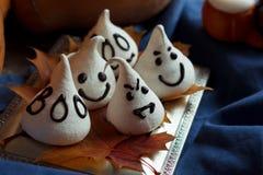 I fantasmi divertenti della meringa per Halloween fanno festa sulle decorazioni di autunno Foglie dorate, zucca, textil blu e luc Immagini Stock Libere da Diritti