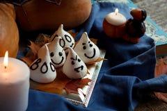I fantasmi divertenti della meringa per Halloween fanno festa sulle decorazioni di autunno Foglie dorate, zucca, textil blu e luc Fotografia Stock Libera da Diritti