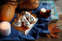 I fantasmi divertenti della meringa per Halloween fanno festa sulle decorazioni di autunno Foglie dorate, zucca, textil blu e luc Immagini Stock