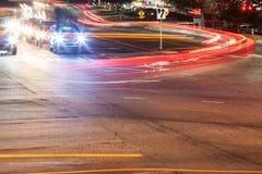 I fari e Brakelights dell'automobile fanno le strisce vaghe moto all'intersezione Fotografia Stock Libera da Diritti