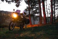 I fari sopra, motociclo di avventura della foresta di notte, ingranaggio del motociclista, un driver della motocicletta guarda, c immagine stock