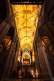 I fasci d'ardore dorati del soffitto estendono attraverso la chiesa Immagini Stock