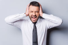 I am fed up with it!. Furious mature man in shirt and tie shouting and covering ears with hands while standing against grey background Royalty Free Stock Photography
