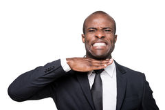 I am fed up with it. Furious young African man in formalwear touching his neck with hand and grimacing while standing isolated on white background Stock Images