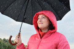 I feel good under the rain. Beautiful young woman wearing a pink anorak hold a black umbrella in autumn surprised and excited under the rain on a fall day Royalty Free Stock Images