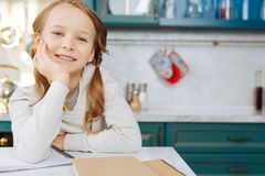 Inspired child sitting at the table with her notebook. I feel happy. Attractive exuberant fair-haired girl smiling and sitting at the table with her notebook and Royalty Free Stock Photo