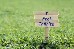 I feel infinite. Wooden sign in grass,blur background Royalty Free Stock Images