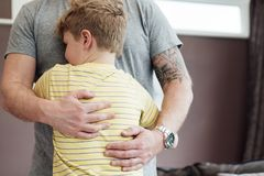 I Feel Safe in Dads Arms. Little boy is cuddling his father at home. He has his arms round his fathers torso and the father is holding his son close to him stock photo