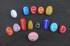 I feel satiated, creative text composed with multi colored and carved sea stones over black volcanic sand. Creative message, I feel satiated, composed with royalty free stock photography