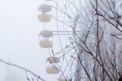 I ferris della ruggine spingono l'attrazione e gli alberi in parco di divertimenti abbandonato l'inverno nebbioso in Pripyt, zona fotografie stock libere da diritti