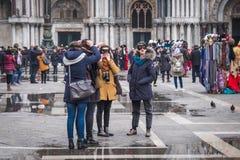 I festaioli di carnevale regolano le loro maschere nel quadrato di St Mark Immagine Stock