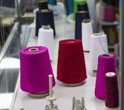 I fili colorati in coni sono su una macchina per maglieria industriale fotografie stock libere da diritti