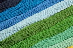 I fili multicolori del cotone per ricamo sono sistemati in una fila Fotografie Stock