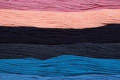 I fili multicolori del cotone per ricamo sono sistemati in una fila Fotografie Stock Libere da Diritti