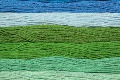 I fili multicolori del cotone per ricamo sono sistemati in una fila Immagini Stock