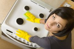 Almost I finished. Young woman in yellow rubber gloves cleaning cooker. Looking at camera. High angle view stock photography