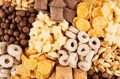 I fiocchi di mais hanno messo - gli anelli, palle, stelle, cioccolato dei cuscinetti, dorato come fondo decorativo dei cereali Fotografia Stock