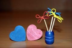 I fiori creativi hanno fatto di gomma e stuzzicadenti rossi e cuori di legno blu sotto forma di un cuore fotografia stock