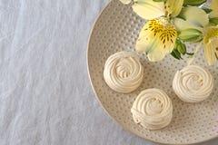 I fiori di Alstroemeria con il piatto agglutina sul fondo bianco della tovaglia Fotografie Stock Libere da Diritti
