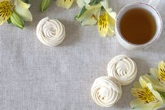 I fiori di Alstroemeria con la tazza di tè agglutina sul fondo bianco della tovaglia Fotografia Stock Libera da Diritti