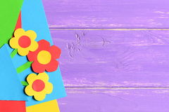 I fiori di carta Colourful, strati di carta su fondo di legno porpora con la copia svuotano lo spazio per testo Carta luminosa de fotografia stock