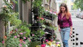 I fiori freschi del deposito della via, una giovane donna sceglie un mazzo video d archivio