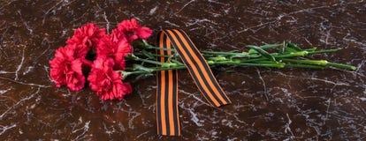 I fiori rossi e un nastro arancio si trovano su una lastra di marmo Fotografie Stock