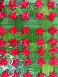 I fiori rossi sistemano sopra permesso verde Fotografie Stock