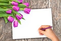 I fiori sulla quercia bruniscono la tavola con il foglio di carta bianco e Han Immagine Stock