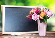 I fiori in vaso e in chalckboard svuotano il fondo dello spazio della copia Fotografia Stock
