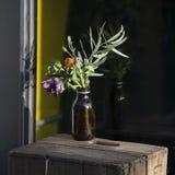 I fiori in vecchie bottiglie della farmacia ornano le stanze frontali di negozio Fotografie Stock