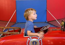 I am a fire man. Cute toddler boy riding a ire-engine in an amusement park stock images
