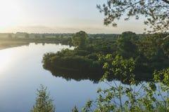 I flussi del fiume di Dnipro al tramonto riflette nelle nuvole Immagine Stock