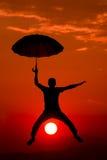 I flyg för ` M med paraplyet royaltyfria bilder