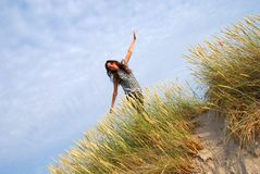 I am flying. The girl running on a sand dune  with blue sky background Royalty Free Stock Images