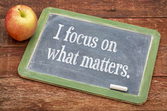 I focus on what matters. Positive affirmation words on a slate blackboard against red barn wood Stock Images