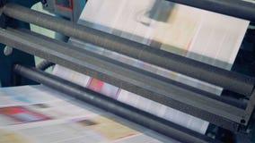I fogli di carta stampati non tagliati stanno passando tramite la macchina tipografica video d archivio