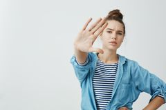 I forbid you to come closer. Studio shot of confident serious woman pulling hand towards camera in stop or enough. Gesture, making warning, wanting person to stock image
