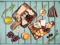 I formaggi assortiti sui piatti del bordo di legno sono servito con i dadi, uva Fotografia Stock