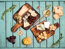 I formaggi assortiti sui piatti del bordo di legno sono servito con i dadi, uva Fotografie Stock Libere da Diritti
